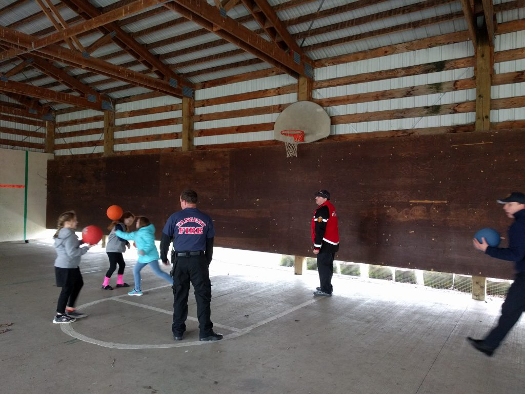 Kids playing basketball with fire fighters